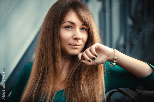 Closeup toned portrait of woman with long hair posing on street