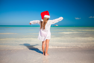 Back view of Little cute girl in red hat santa claus on the