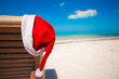 Close-up of santa hat on chair longue at tropical caribbean