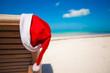 Close-up of santa hat on chair longue at tropical caribbean