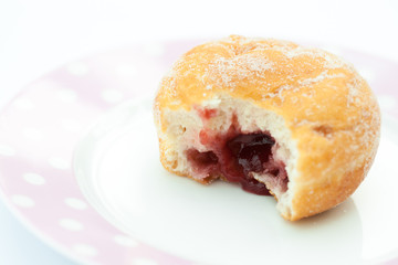 Jam doughnut with a mouthful taken out and jam showing