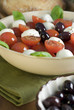 healthy salad with tomato, mozzarella, basil and olives.