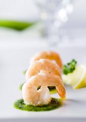 Closeup of three fried shrimp with pesto.