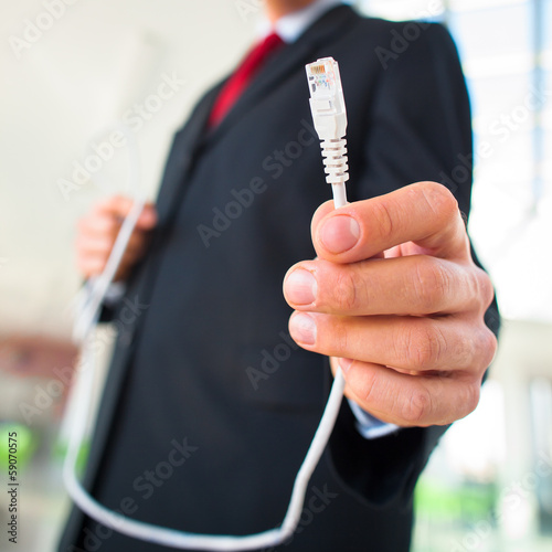 Young businessman holding an ethernet cable