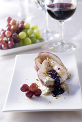 Baked pear stuffed with Gorgonzola and blackberry sauce.