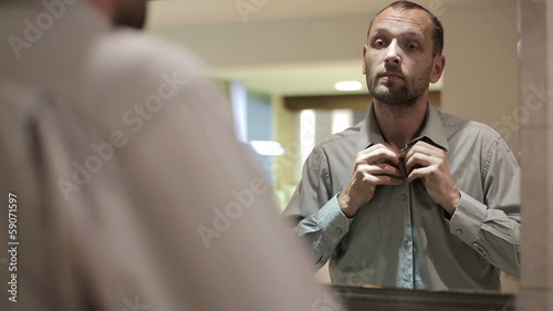 Businessman wearing collar shirt in front of the mirror