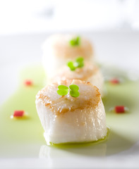 Closeup of scallop appetizers in fresh chive oil.