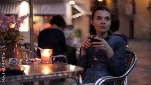 Young, pensive woman drinking red wine at the cafe by night