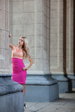 Beautiful woman in pink dress among columns.