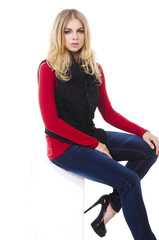 girl with long hair is in fashion style in jeans sitting cube