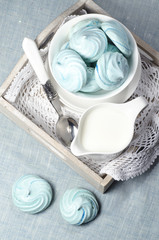 Azure homemade meringue cookies and cup of milk