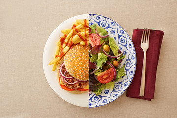 Low fat salad against greasy burger