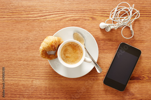 Having coffee and croissants with smartphone