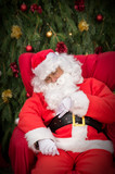 Sleeping Santa Clause on red Christmas armchair