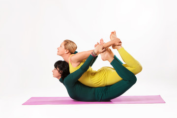senior and younger woman practice yoga