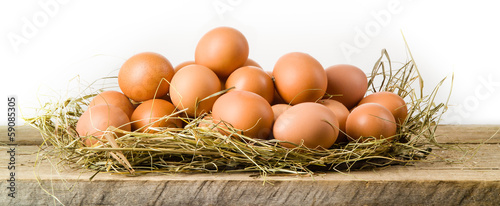 Chicken eggs in hay nest. Isolated on white. Organic food