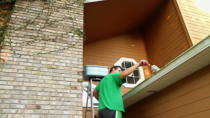 30's Adult Male Cleaning Gutters On Home