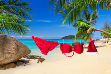 Santa hat and red bikini hanging on the tropical beach