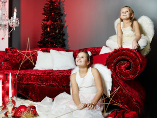Two girls as angels are waiting for Santa Claus