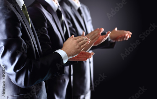 Male hands clapping on black, side-view