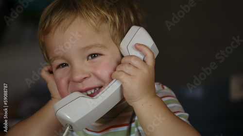 Excited little boy talking over telephone receiver
