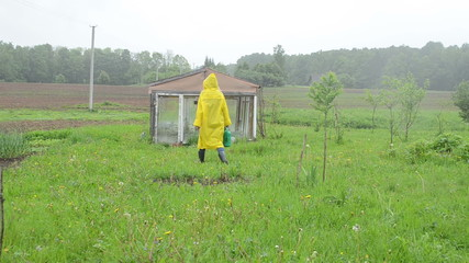 Woman in waterproof coat with watering-can to garden greenhouse