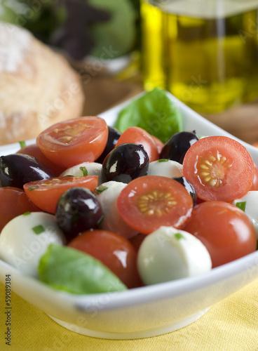 salad with tomato, mozzarella, basil and olives.