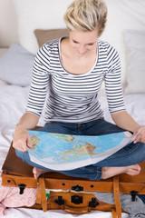 frau sitzt auf koffer und studiert landkarte