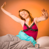 Preety woman stretching arms after waking up in early morning