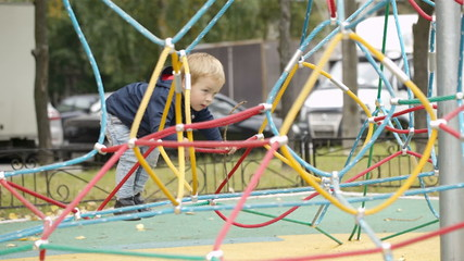 Happy little boy climbing on playground equipment