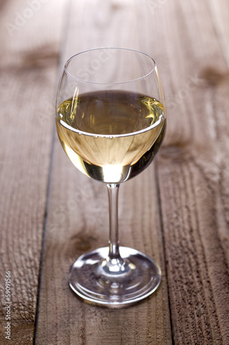 Glass of white wine sitting on a rustic wooden surface.