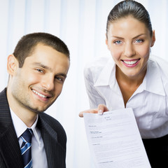 Two businesspeople with document at office