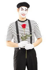 Male mime artist holding a rose flower