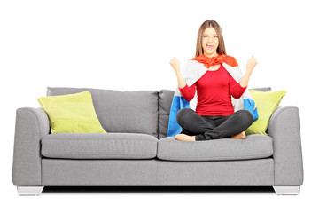 Young female sport supporter sitting on a modern sofa and cheeri