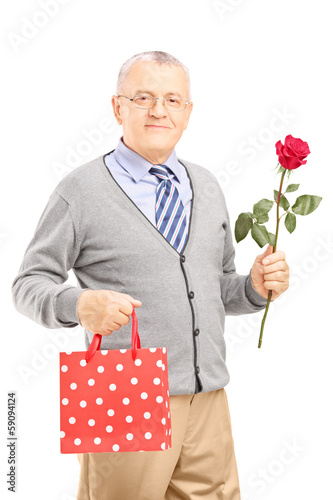Mature gentleman holding a rose flower and bag