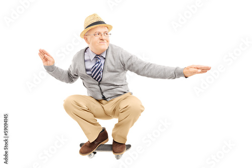 Senior man with hat riding a skateboard