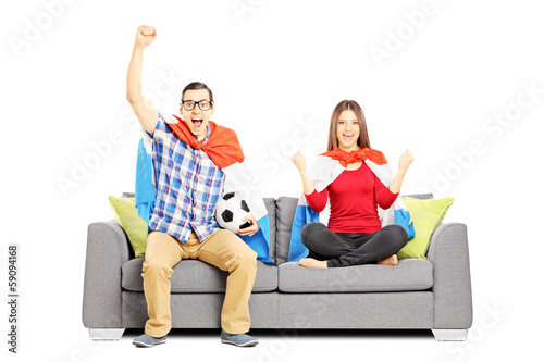 Young football supporters sitting on a modern sofa