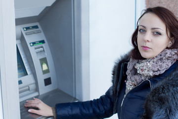 Young woman standing at an ATM machine