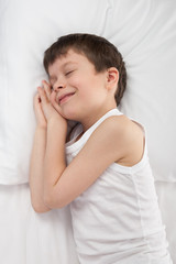 cheerful boy sleep in white bed