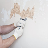Hand removing wallpaper from wall