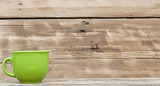 Green mug on wooden table over wood background