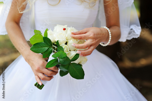 bridal bouquet of white roses in bride's hands