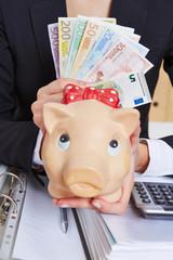 Hand holding piggy bank and Euro money bills