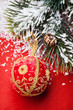 Christmas ball and green spruce branch on red background
