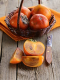 persimmon fruit whole and sliced on a wooden table