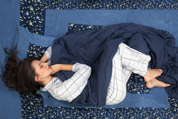 Woman sleeping in curled position, comfort in bed