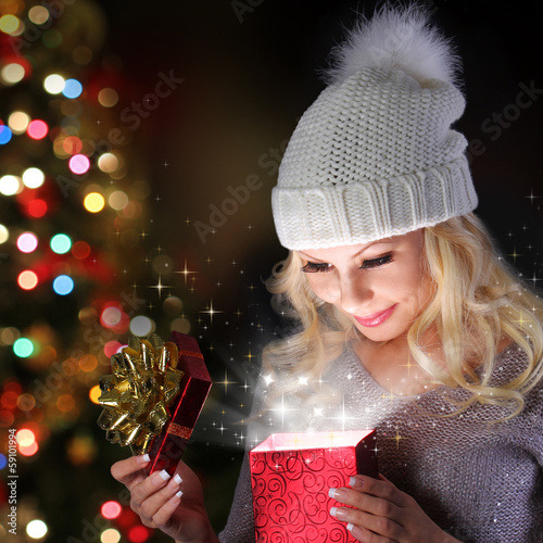 Christmas Miracle. Smiling Girl with Knitted Hat Opening Gift