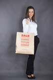 Attractive business woman with paper shopping bag