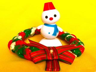 首を傾げる雪だるまとクリスマスリース