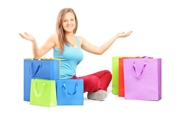 Young smiling woman sitting on a floor with many shopping bags